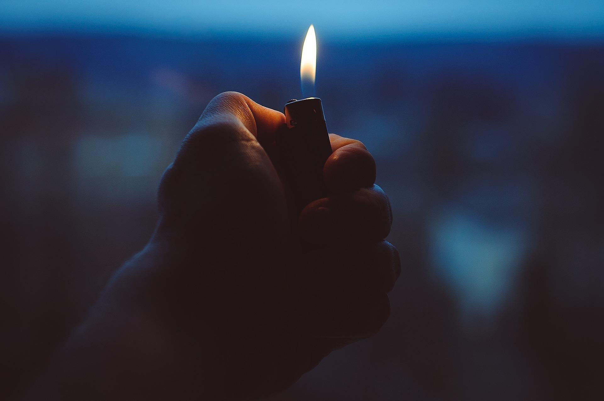 main qui tient un briquet à la tombée de la nuit